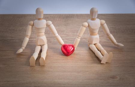 Ein paar hölzerner Puppenmann an den Valentinsgrußtagen, die sich Liebe mit einander zeigen und konzentrieren sich entweder auf Herz-förmige Schokolade und die Paare Standard-Bild