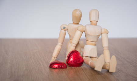 cuteness: A couple of wooden doll man on valentine days showing love to each other and focus either on heart-shaped chocolate and the couple Stock Photo