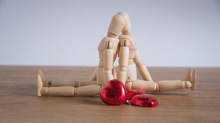 Ein paar hölzerne Puppe Mann an den Tagen Valentin Liebe zueinander und den Schwerpunkt entweder auf herzförmige Schokolade und das Paar