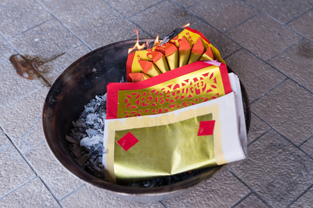 believing: A burning golden paper. A chinese ritual to pay respect to the ancestor, believing that the prosper will be sent to the their gone beloved