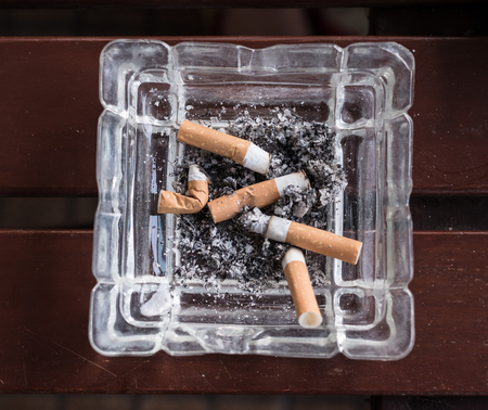 the ashes: cigarette stub with ashes in the ashtray. Smoke and cancer.