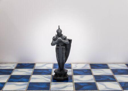 A morceaux de caractère d'échecs sur le plateau avec une lumière. Un personnage représente la stratégie, la planification, courageuse, la trahison, la confrontation et la concurrence.