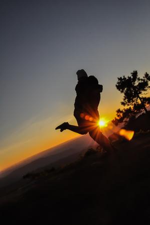 Love couple silhouette sunset on the mountain photo