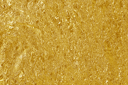 Gold foil leaf shiny texture, abstract yellow wrapping paper for background and design art work. 스톡 콘텐츠