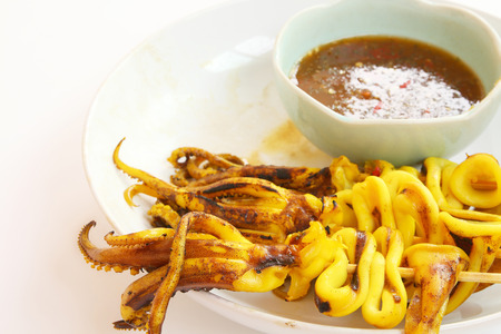 Grilled squid and seafood sauce on white color plate with copy space. Stock Photo
