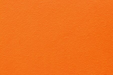 Orange color concrete cement wall with detail of rough stucco for background and design art work. Stok Fotoğraf