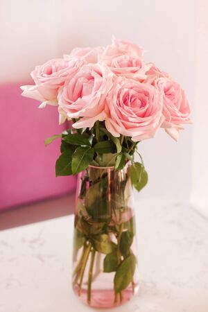 Close up of beautiful bouquet of pink roses in glass vase on white marble table at living room. Stok Fotoğraf