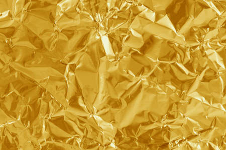 Gold foil leaf shiny texture, abstract yellow wrapping paper for background and design art work. Imagens