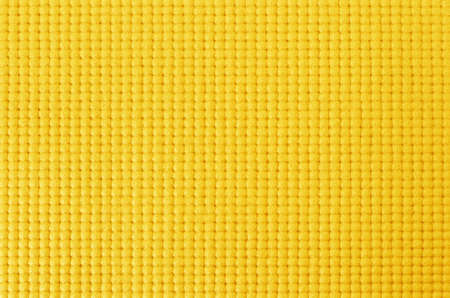 Texture of yellow color yoga mat for background and design art work.