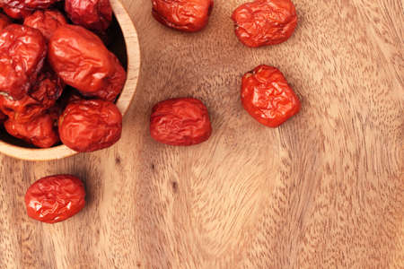 Close up of red jujube fruit on wooden background with copy space.