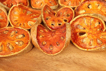 Close up of slices dried bael fruit on wooden background.