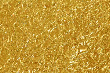 Gold foil leaf shiny texture, abstract yellow wrapping paper for background and design art work. 免版税图像