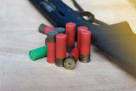 Close-up of ammo and shotgun on wood floor with selective focus.