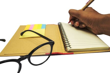 hand writing notes with black eyeglasses on the book and multicolor postit on white