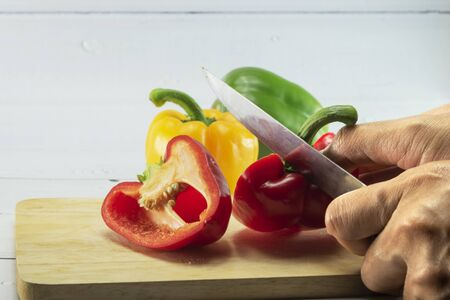 Closeup of woman's hand slicing Red, Yellow, Green, bell pepper or sweet pepper or capsicum on chopping wood on white background with selective focus,raw food ingredient concept.