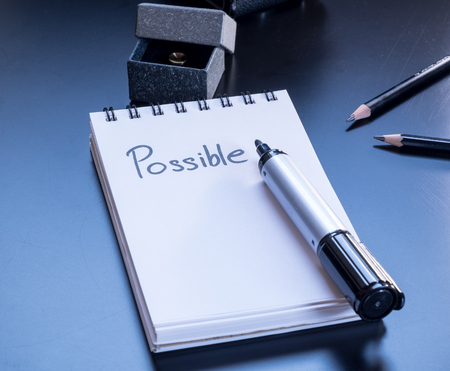 board marker: Possible is written on small notepad with a board marker, pencil and giftbox on PVC black