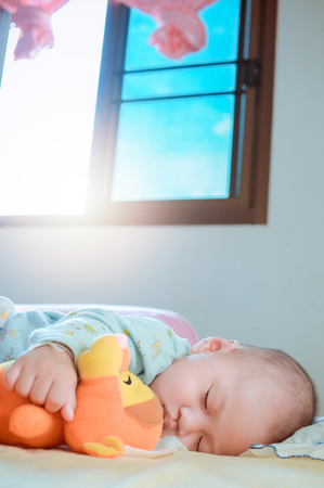 Sleeping baby in bed  holding doll.