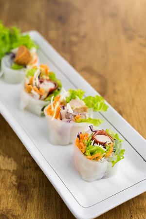 Portion of spring rolls , vegetables and in noodle tube