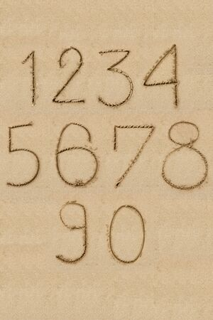 Numbers one to zero written on sand