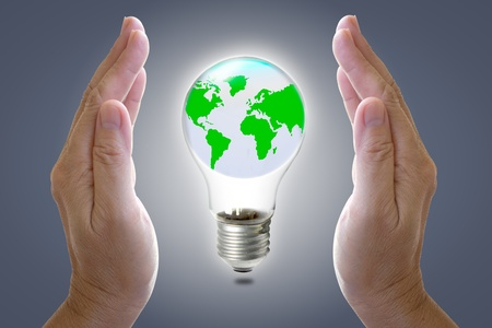World in light bulb and hands for protect photo