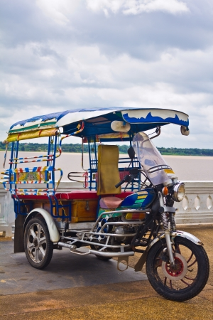 tuk: Tricycle in Thailand with Mae Khong River. Stock Photo