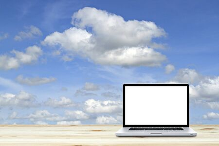 Laptop computer on wooden floor with sky  background. White screen Stock Photo