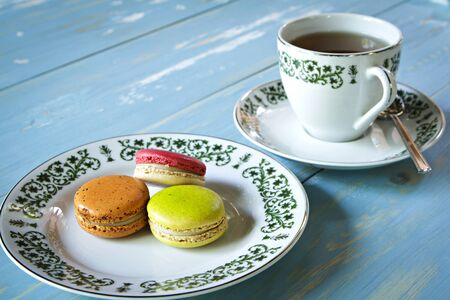 Macarons with a cup of tea on wooden table.