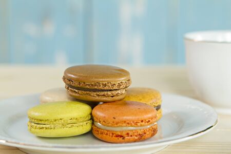Macarons on white dish and coffee cup.