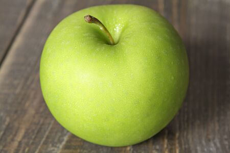 Green apple on wooden background. Stock Photo