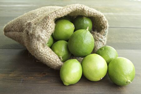 Limes in small sack on wooden background.