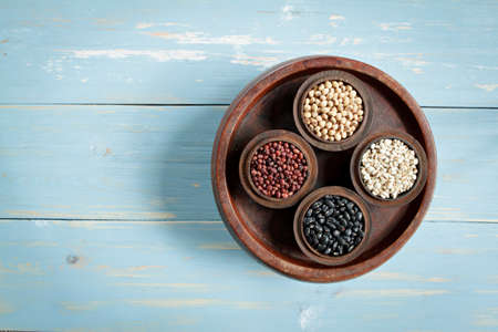 Red Beans, black beans, millet and  black eyed peas in wood bowl set on wood background. Stock Photo
