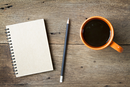 Koffie en notebook op houten achtergrond