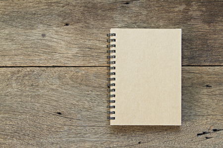 business book: Brown notebook on wooden background