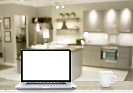 Laptop white screen and coffee cup on marble table with kitchen background.