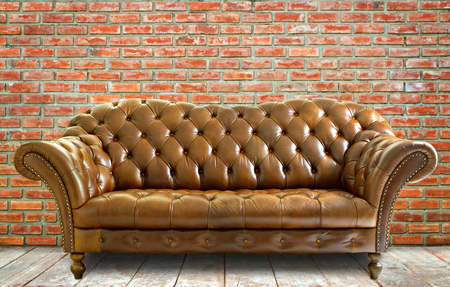 sitting on floor: Vintage style  leather sofa with wooden floor and brick wall. Stock Photo