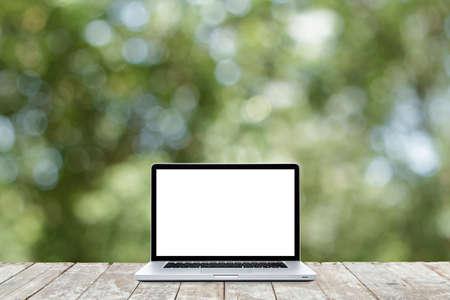 defocus: Laptop computer on wooden floor with defocus of garden background