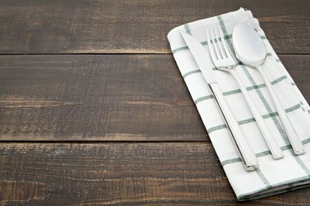 grunge flatware: Silverware and napery on wooden background.