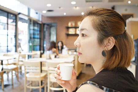 Beautiful girl with coffee cup feeling alone in coffee shop Stock Photo