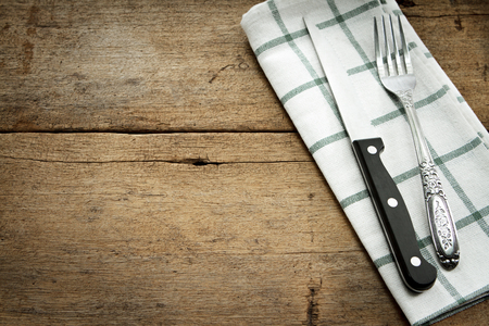 grunge flatware: Cutlery and fork with napery  on wooden background.