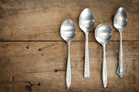 stainless steel background: Vintage spoons on wooden background.