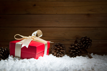 festive pine cones: Red gift box on snow with wooden background.