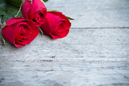 Red roses on woonden background. Valentines day background.
