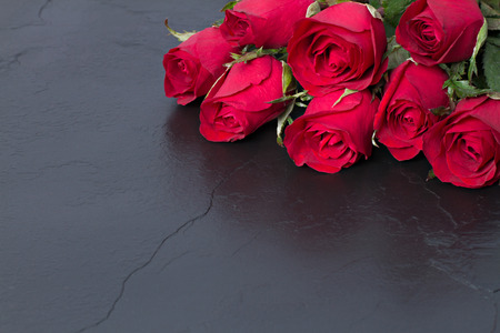 red stone: Red roses on black stone background. Valentines day background. Stock Photo