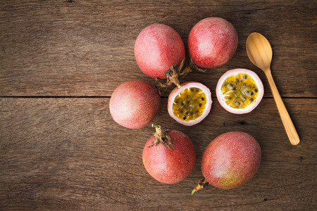Passion fruits and slice with wooden spoon on wooden background.