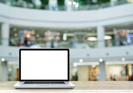 departmentstore: Laptop computer on table with de focused of departmentstore.