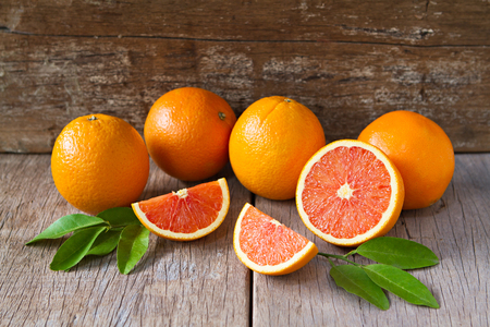 Fresh oranges with slices and leaves on wooden background. Banco de Imagens