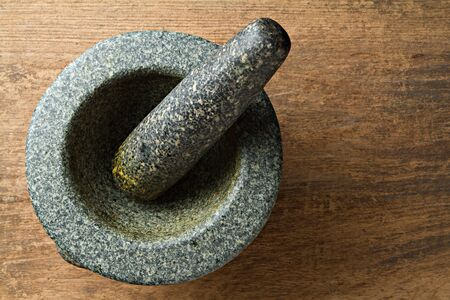 Granite mortar on wooden background. Stock Photo