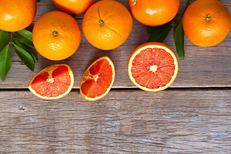Fresh oranges with slices and leaves on wooden background. Stock Photo