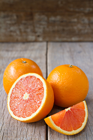 Fresh oranges with slices on wooden background.
