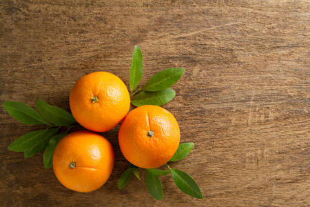 Fresh oranges with  leaves on wooden background. Stock Photo